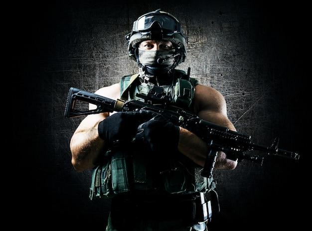 De soldaat van de speciale eenheid staat met een automatisch wapen in het voordeel. gemengde media