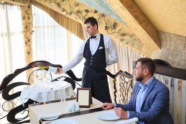 De sommelier giet de wijn in de karaf bij de gast in het restaurant.