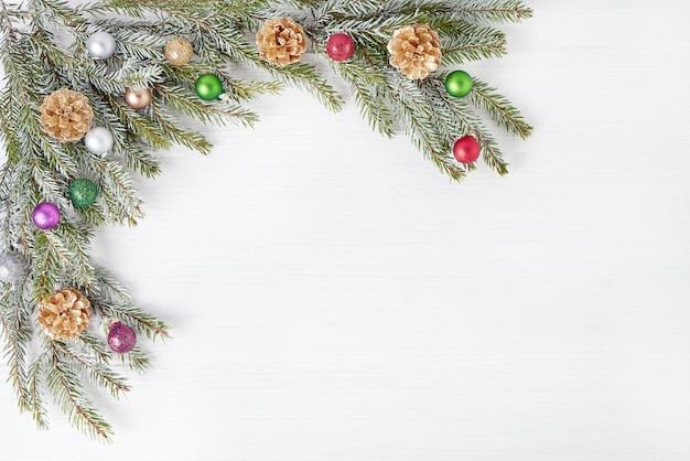 De sparrentakken van kerstmis die met gouden kegels op witte houten achtergrond worden verfraaid. copyspace