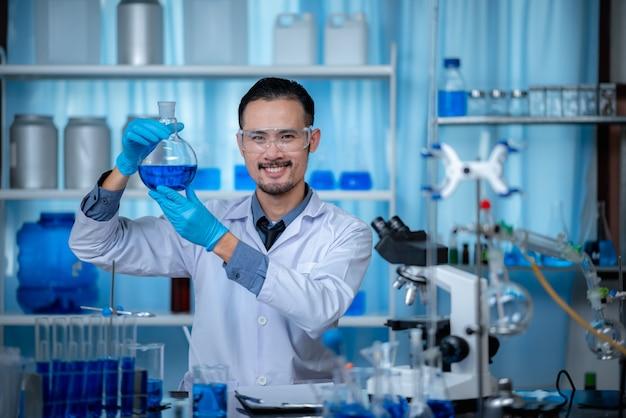 De speciale jonge mannelijke scientis of onderzoeker die de chemische oplossing door de reageerbuis kijkt voor het ontwikkelen van vaccinexperimenten in het moderne biologische laboratorium