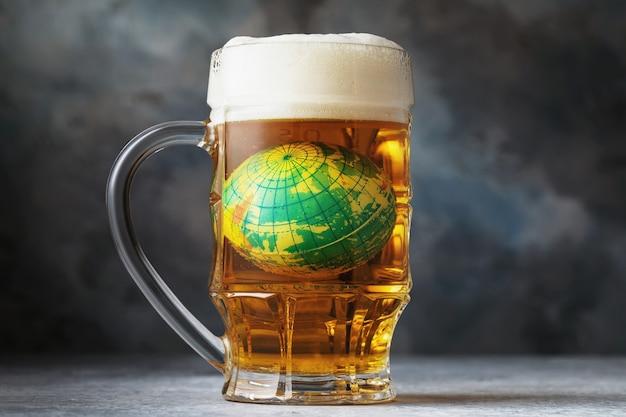 De speelgoedbol verdrinkt in een mok bierconcept van alcoholisme over de hele wereld