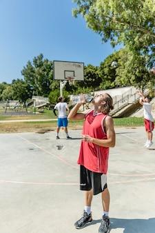 De speler drinkwater van de basketbal van fles bij openluchthof