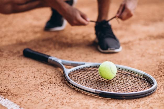 De speler van het jonge mensentennis bij het hof, dichte omhooggaand van de tennisracket