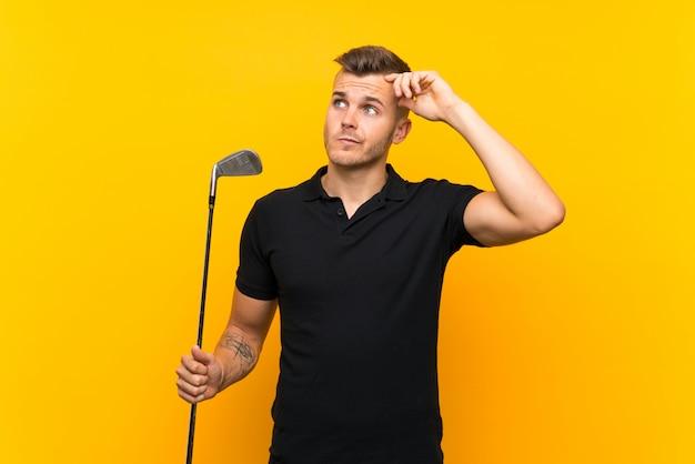De spelermens van de golfspeler over geïsoleerde gele achtergrond die twijfels hebben en met verwarren gezichtsuitdrukking