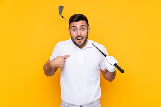 De spelermens van de golfspeler over geïsoleerde gele muur met verrassingsgelaatsuitdrukking