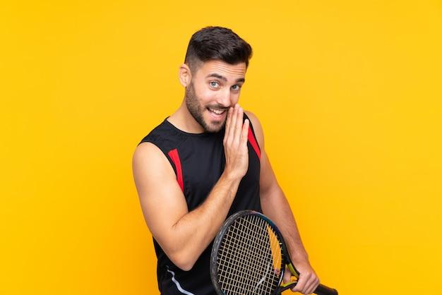 De spelermens van het tennis over geïsoleerde gele muur die iets fluistert