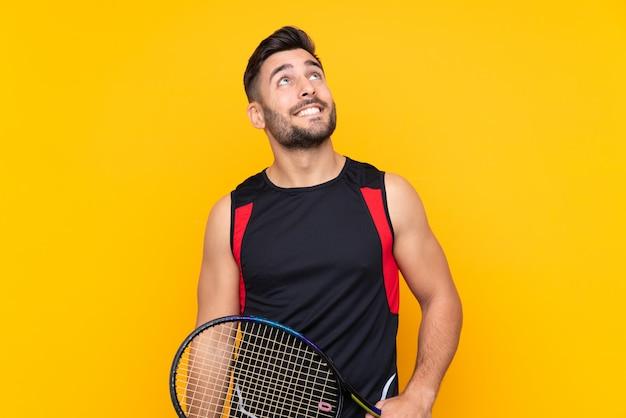 De spelermens van het tennis over geïsoleerde gele muur die omhoog terwijl het glimlachen kijkt