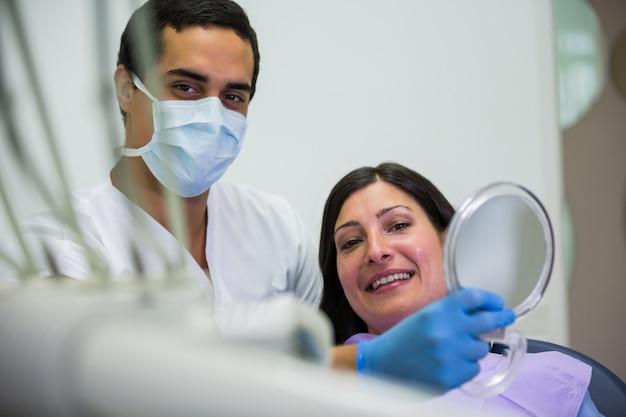 De spiegel van de tandartsholding voor patiënt