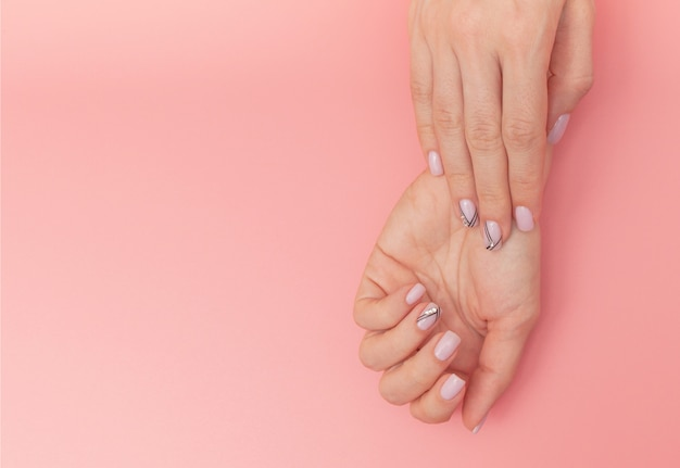 De spijkers van de mooie vrouw met aardige modieuze manicure op roze