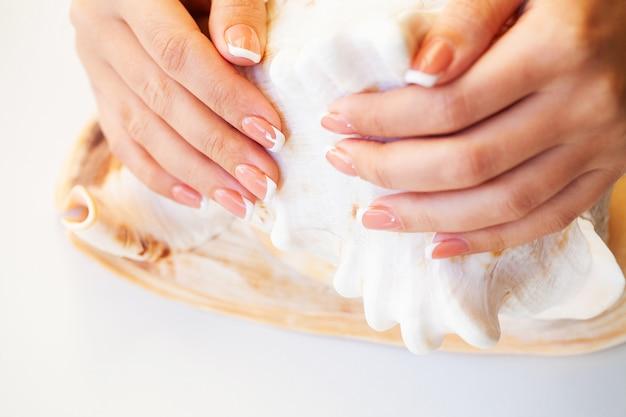 De spijkers van de mooie vrouw met franse manicure, in schoonheidsstudio