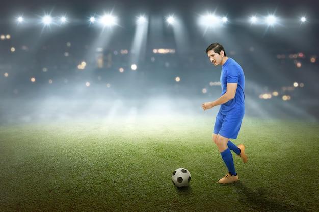 De spirituele aziatische mannelijke voetballer schopt de bal