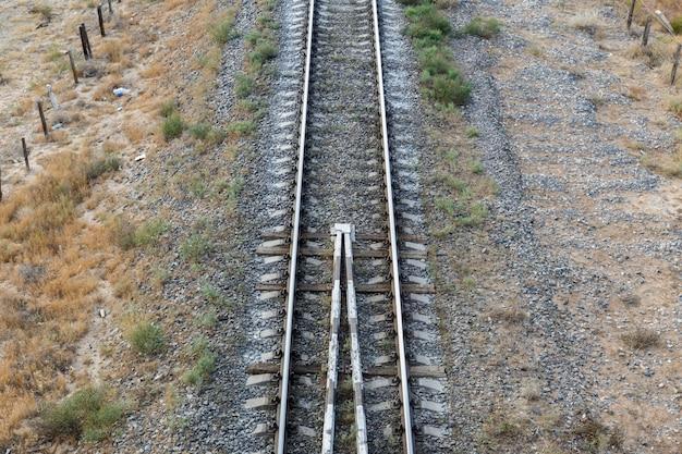 De spoorlijn in de steppe van kazachstan, uitzicht op de rails vanaf de brug