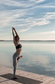 De sportdame die zich bij het strand bevindt maakt yogaoefeningen.