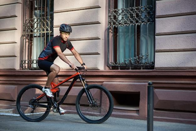 De sportieve berijdende fiets van de kerelfietser langs historisch oud gebouw