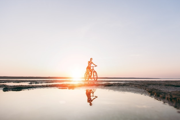 De sportieve blonde vrouw in een kleurrijk pak fietst op een zonnige zomerdag in een woestijngebied in de buurt van het water. fitness concept... reflectie in water