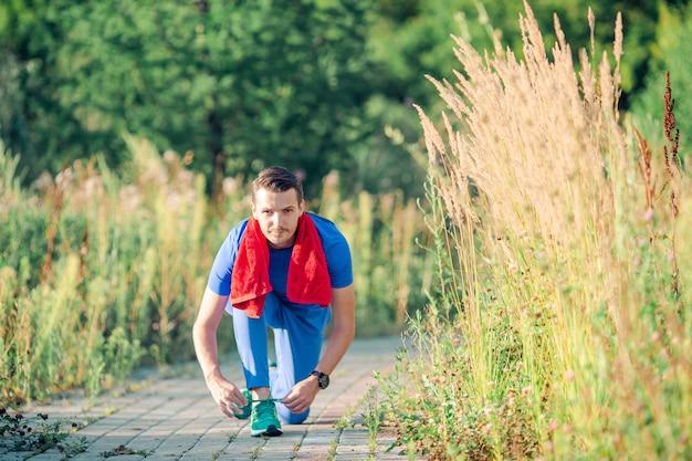 De sportieve jonge mens die sport doet oefent in openlucht in het park uit