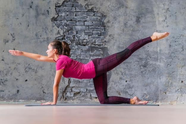 De sportieve jonge vrouw die chakravakasana doet stelt