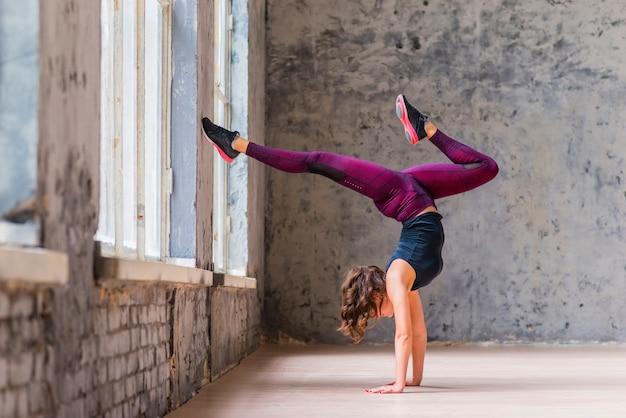 De sportieve jonge vrouw die naar beneden toegekeerde boom doen stelt in zolder