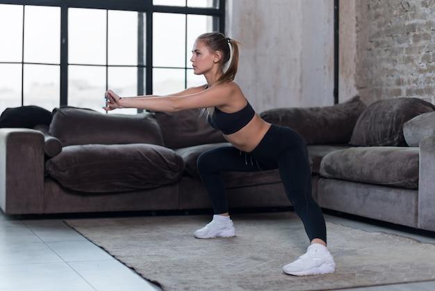 De sportieve kaukasische vrouwelijke atleet in zwarte sportenbustehouder en beenkappen die zij hurkende oefening thuis doen
