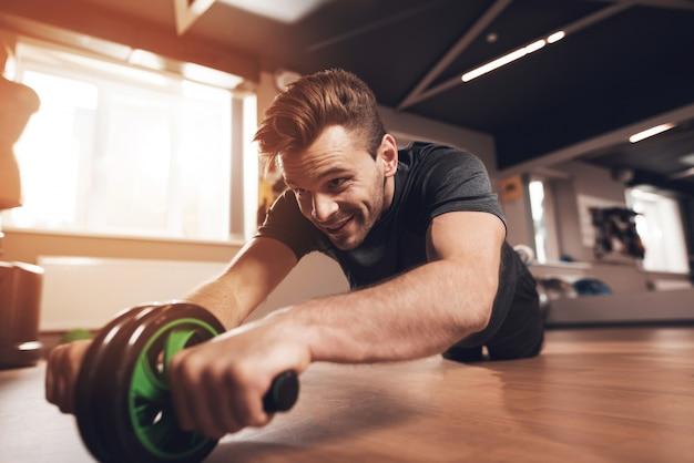 De sportieve mens doet oefeningen met het gymnastiekwiel.