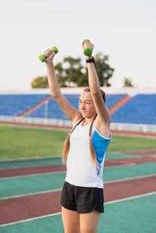 De sportieve vrouw bij stadionhanden oefent uit