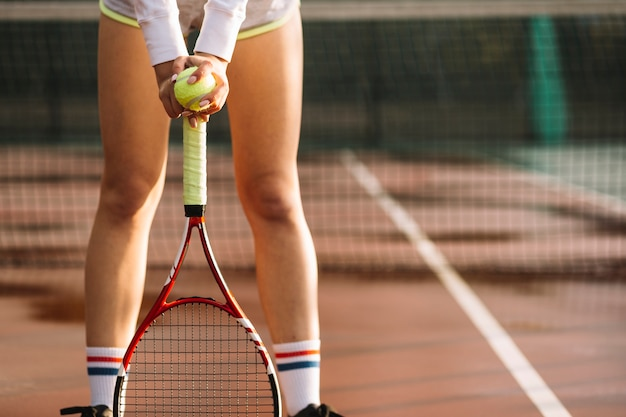 De sportieve vrouw rust op de tennisracket