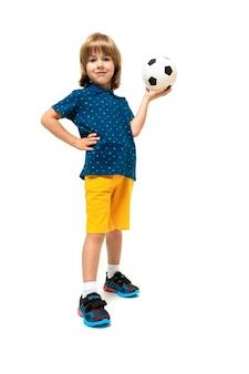 De sportjongen houdt een voetbalbal in zijn handen op een wit