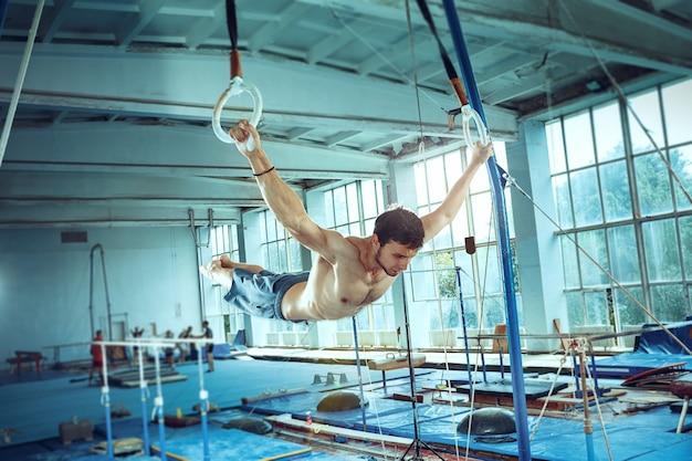 De sportman die moeilijke gymnastiekoefeningen uitvoert in de sportschool. de sport, oefening, gymnast, gezondheid, training, atleet concept. kaukasisch fit model