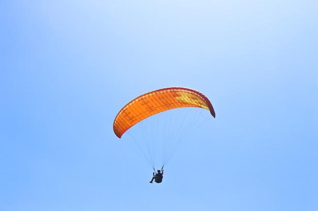 De sportman die op een paraglider in de blauwe lucht vliegt