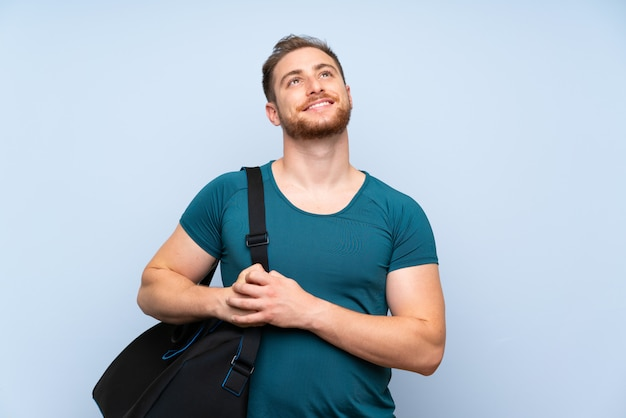 De sportmens die van de blonde over blauwe muur omhoog terwijl het glimlachen kijkt