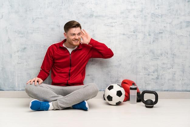 De sportmens die van de roodharige aan iets luistert door hand op het oor te zetten