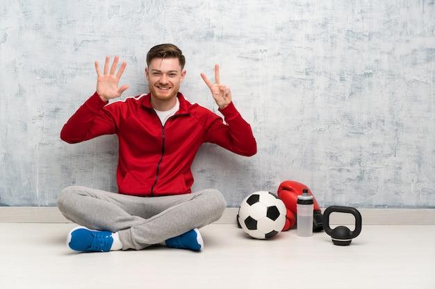 De sportmens die van de roodharige zeven met vingers telt