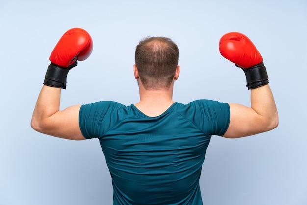De sportmens van de blonde over blauwe muur met bokshandschoenen