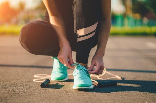 De sportvrouw bindt schoenveters op tennisschoenen en treft voorbereidingen om in openlucht touw te springen