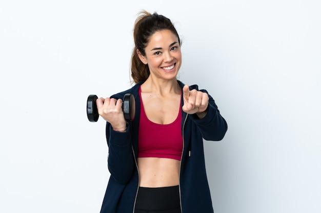 De sportvrouw die gewichtheffen over geïsoleerde witte muur maken richt vinger op u met een zekere uitdrukking