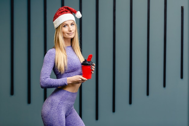 De sportvrouw die santahoed draagt houdt waterfles