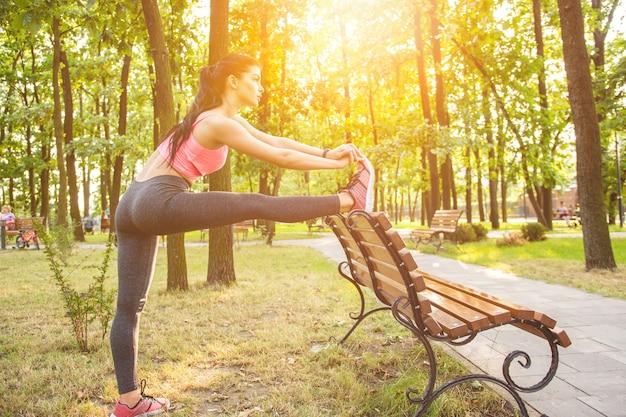 De sportvrouw doet oefening in de parkbank