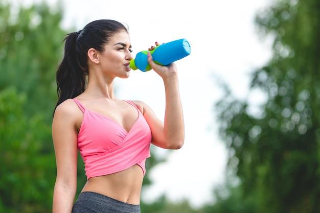 De sportvrouw drinkt een water op de boomachtergrond
