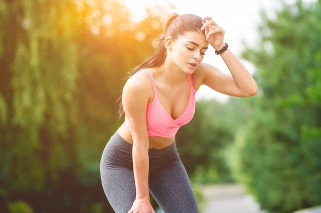 De sportvrouw ontspant op de zonneschijnachtergrond