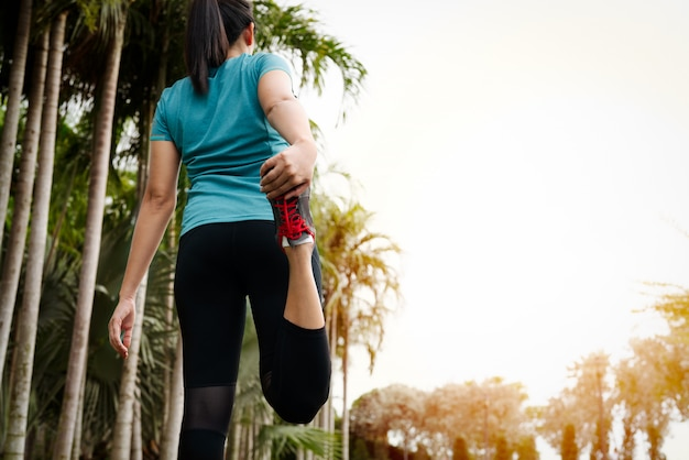 De sportvrouw rekt spier vóór training uit