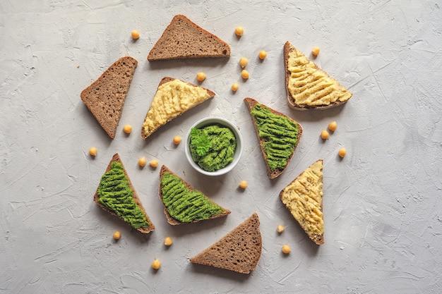 De spread op het brood van kikkererwten. verschillende dip sauzen op grijze tafel, bovenaanzicht