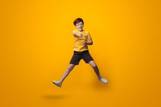 De springende jongen met rood haar draagt een bril en wijst op de camera die een geel overhemd op een studiomuur draagt