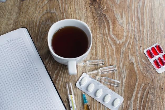 De spuit op het bureaublad van de dokter op het notitieboekje met de ecg