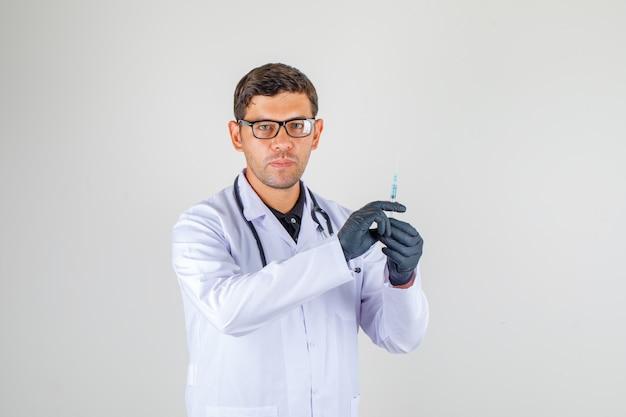 De spuit van de artsenholding terwijl het bekijken camera in witte laag met stethoscoop