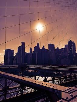 De stad van new york van de brug van brooklyn bij zonsondergang
