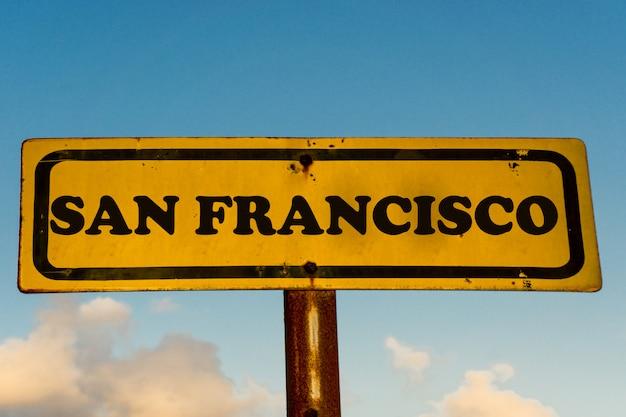 De stads oud geel teken van san francisco met blauwe hemel