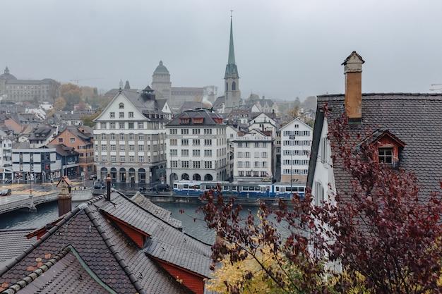De stadscentrum van zürich mening over het rivierpanorama van limmat op het gebouw, bewolkt weer