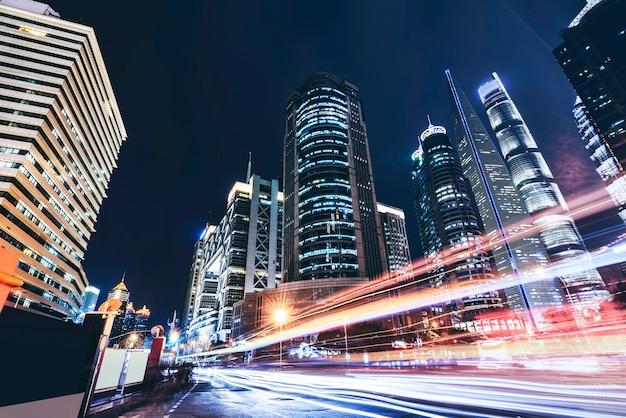 De stadsgebouwen van shanghai bij nacht en vage autolichten