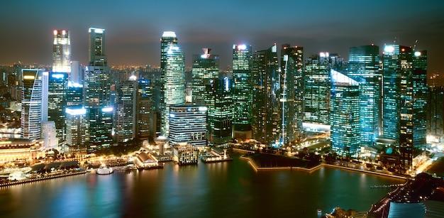 De stadslandschap van singapore met wolkenkrabbers die bij nacht worden verlicht