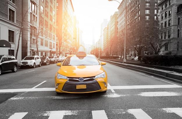 De stadstaxi van new york in gele kleur in het verkeerslicht